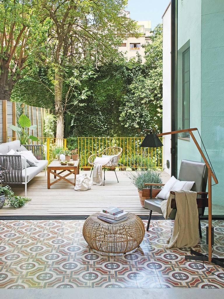 Кресло и лампа середины 20-го века и сдвижные стеклянные двери на террасу.