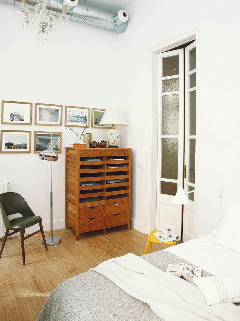 Остекленная дверь призвана пропускать свет в коридор, где нет окон. Стоит обратить внимание на то как дизайнер сочетает открытый блестящий воздуховод с хрустальной люстрой, деревянный комод напоминающий картотеку из старого офиса с модернистской лампой.