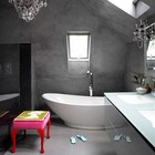 Эклектичная ванна с бетонными стенами, хрустальными люстрами и ярким табуретом