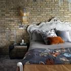 Кровать с стиле барокко резко контрастирует с кирпичной стеной. (индустриальный,лофт,винтаж,стиль лофт,индустриальный стиль,архитектура,дизайн,экстерьер,интерьер,дизайн интерьера,мебель,эклектика,смешение стилей,спальня,дизайн спальни,интерьер спальни)