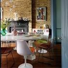 Столовая с викторианским камином, кирпичной стеной и эклектичной мебелью.
