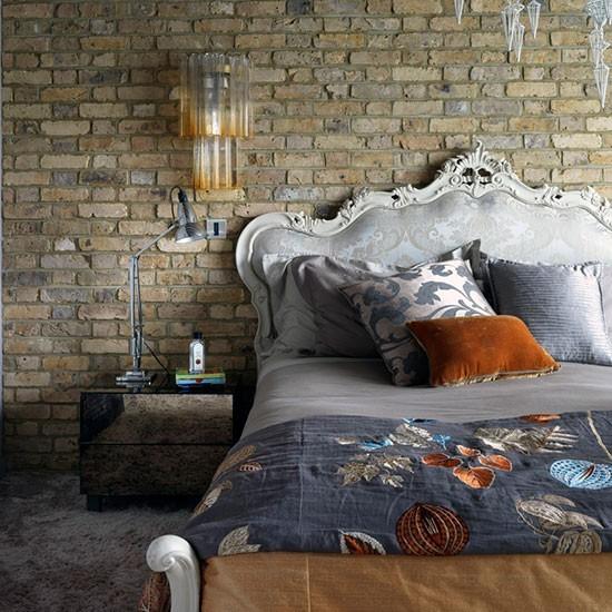 Кровать с стиле барокко резко контрастирует с кирпичной стеной.