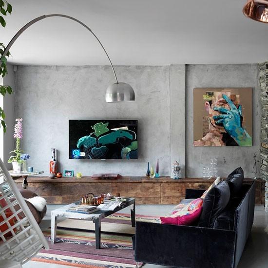 Несмотря на брутальную серую стену и полку вдоль всей стены из состаренного дерева, в гостиной уже просматриваются элементы традиционной английской эклектики. Такие например блестящий журнальный столик в центре и круглый столик у окна.