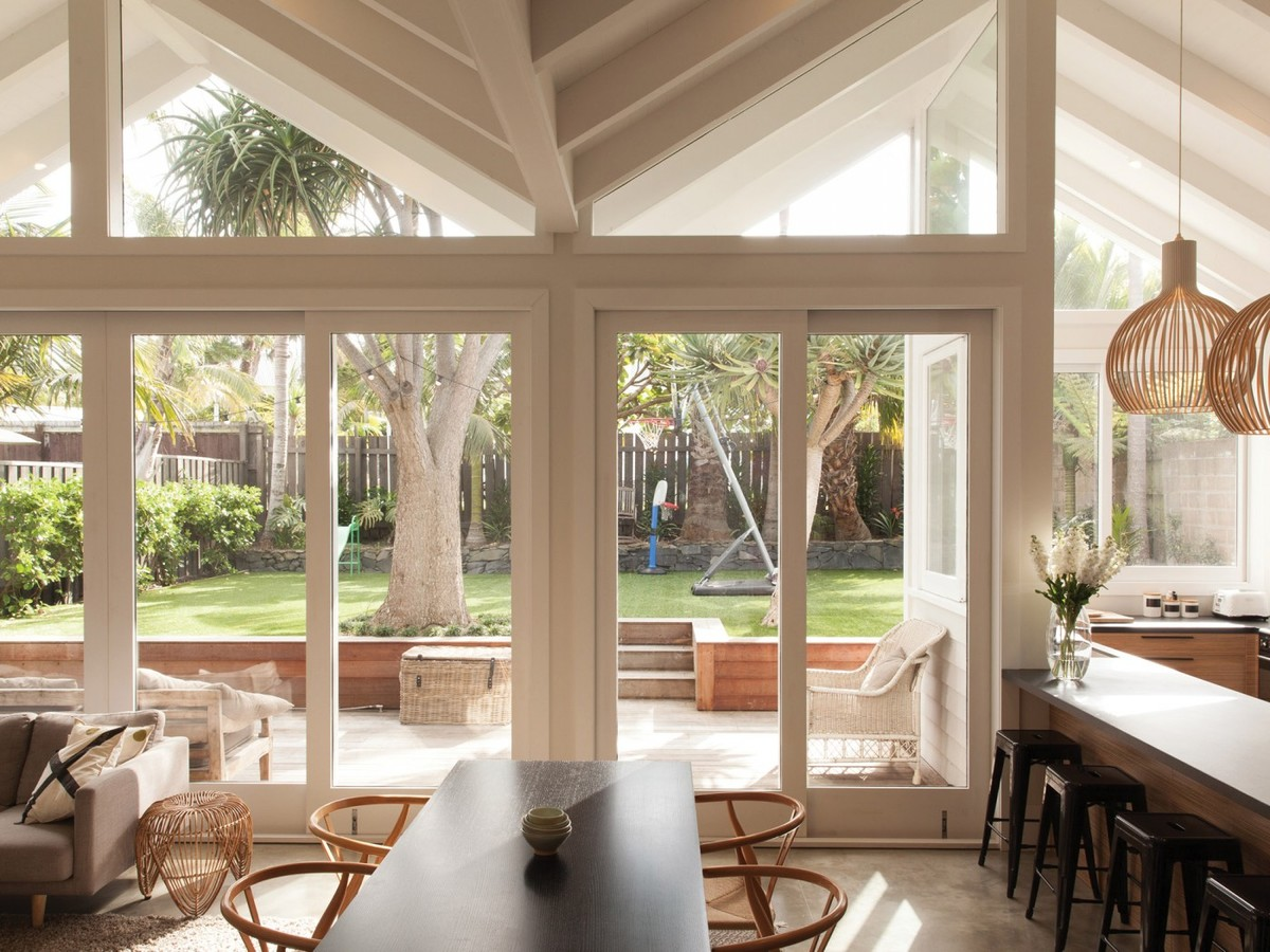 Гостиная, столовая и кухня образуют единое жилое пространство, а большая площадь остекления визуально присоединяет к нему террасу.