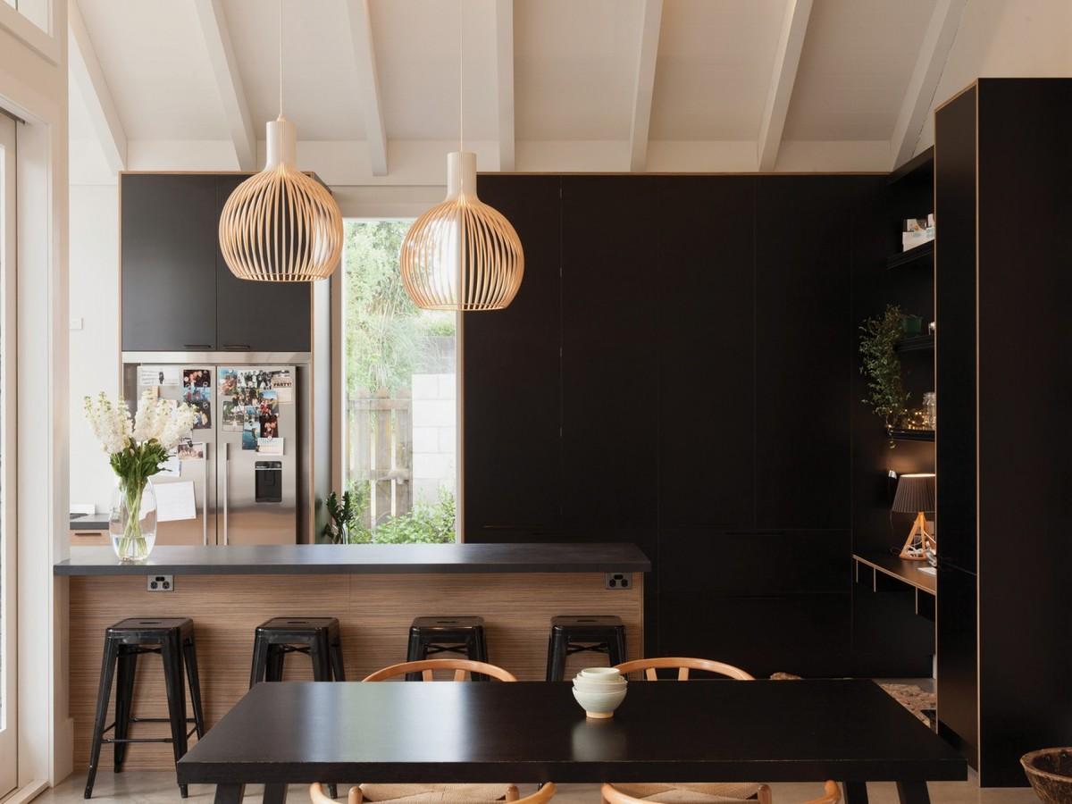 Кухонные фасады черного цвета противопоставляют кухню остальной части жилой комнаты, визуально объединяя ее со столовой.