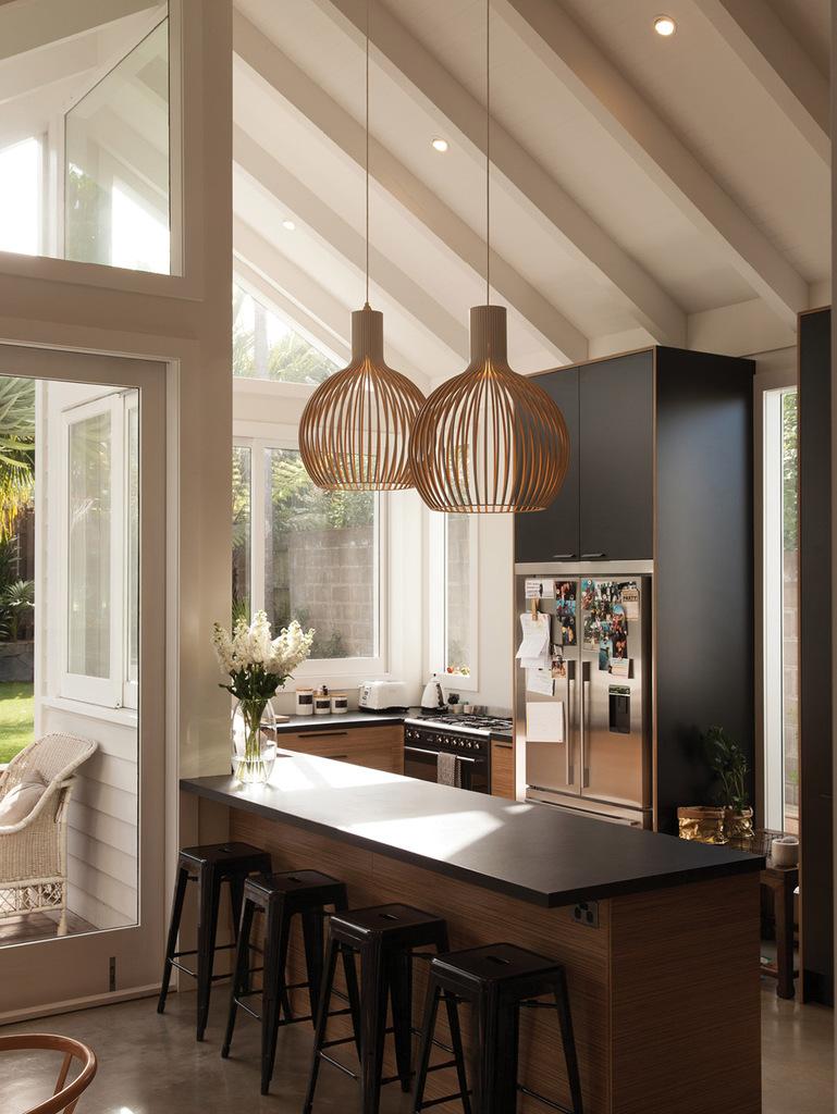 Отлично смотрится кухня с темной мебелью, контрастными светлыми стенами и большой площадью остекления.