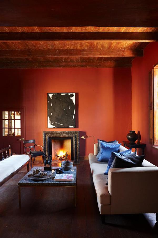 В гостиной красные стены. На окнах деревянные ставни защищающие комнаты от жары летом, а камин согревает зимой.