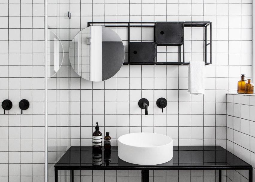 Мебель в ванной главной спальне повторяет сетчатую структуру стеллажа в жилой комнате, только окрашена в контрастный черный цвет.