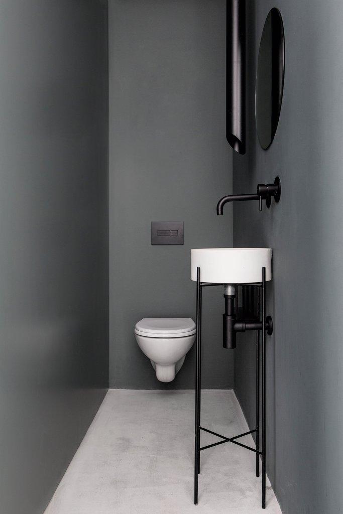 Серый туалет рядом с гостиной.