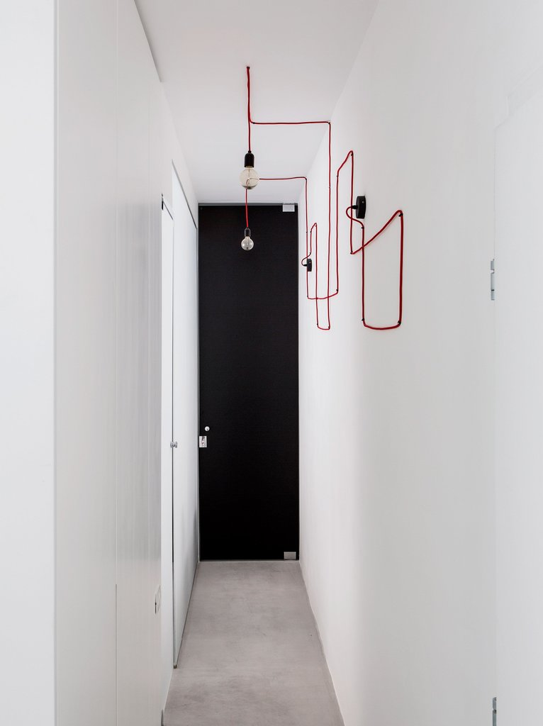 Узкий коридор ведущий к спальням украшен витиевато уложенным в геометрические фигуры красным проводом для ламп