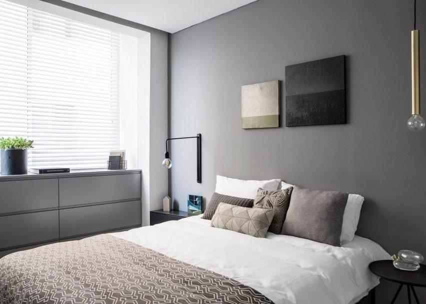 В главной спальне прикроватные светильники разные. Один - черный настенный, а второй, похожий на латунный кулон, свисает с потолка.