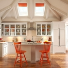 Совпадение цвета рулонных штор на мансардных окнах, барных стульев и некоторой посуды объединяет интерьер этой кухни.
