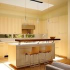 Световое окно в потолке кухни ярко освещает кухонный остров, а отраженный свет освещает и прилегающую гостиную.