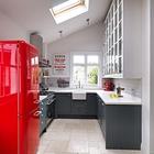 Великолепная кухня с серыми шкафами и красным акцентом в виде холодильника. Световое окно улучшает восприятие небольшого пространства.