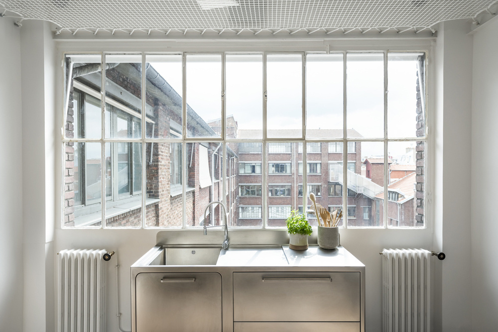 Кухонная раковина из нержавейки у окна отлично гармонирует с винтажной формой оконной рамы.