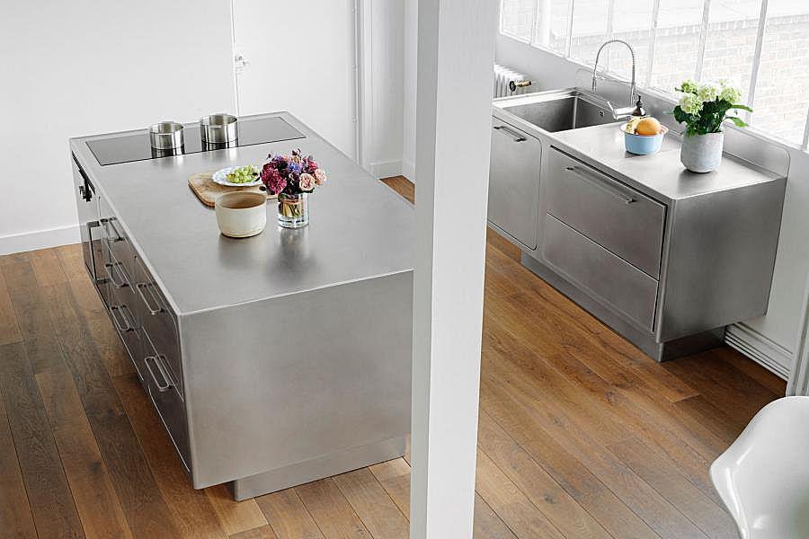 Минималистичная и стильная кухонная мебель из нержавейки украшает жилую комнату, куда входит кухня.