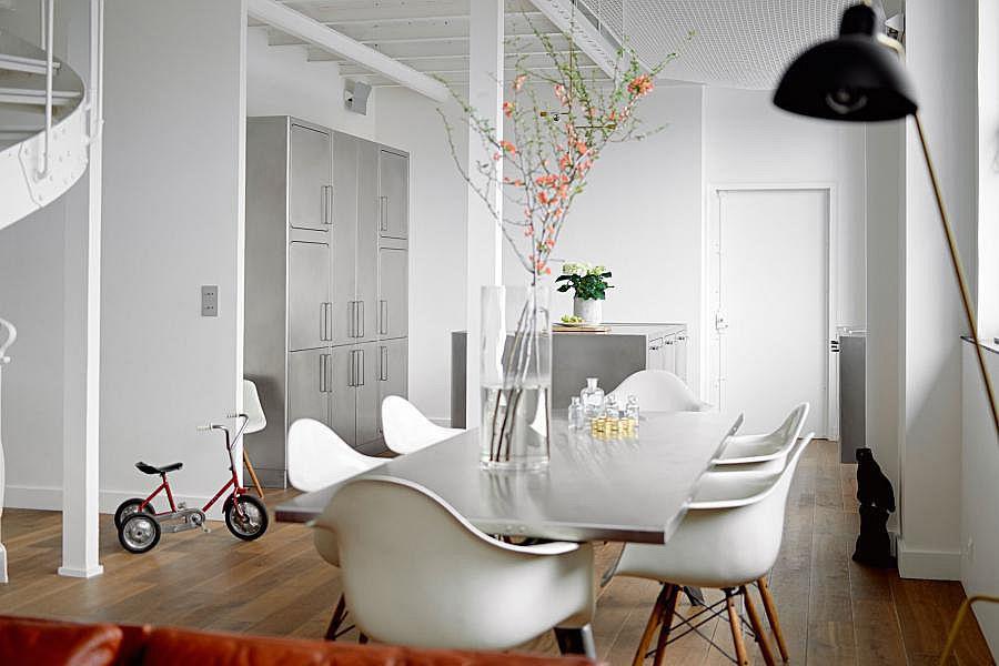 Обеденный стол в столовой также имеет столешницу обшитую нержавейкой. При открытой планировке это добавляет связь между кухней и столовой.