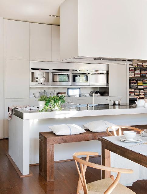 Рабочей поверхностью в кухне служит бетонный кухонный остров со столешницей покрытой нержавейкой. Он же служит и барной стойкой. Вместо барных стульев дизайнер использовал скамью.