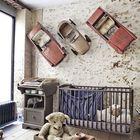 Декоративные элементы из машинок на стене делают эту детскую в стиле лофт абсолютно уникальной.