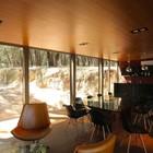 Кухня и столовая в доме отделаны панелями темного дерева. (минимализм,архитектура,дизайн,экстерьер,интерьер,дизайн интерьера,мебель,кухня,дизайн кухни,интерьер кухни,кухонная мебель,мебель для кухни,гостиная,дизайн гостиной,интерьер гостиной,мебель для гостиной,столовая,дизайн столовой,интерьер столовой,мебель для столовой)