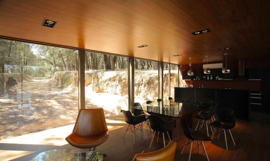 Кухня и столовая в доме отделаны панелями темного дерева.