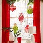 Декор из хвои и вырезанных из ткани елочных игрушек в традиционных новогодних цветах украшают это окно.