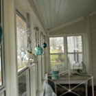 Елочные игрушки на окнах на веранде.