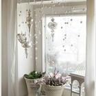 Гирлянда из белых шариков и серебристые елочные украшения в спокойном скандинавском стиле.