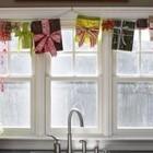 Гирлянда из подарочных коробок и елочка на подоконнике украшают кухонное окно.