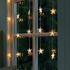 Гирлянда из светящихся звездочек и фигурки на подоконнике меняют восприятие окна.