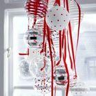 Гроздь елочных шаров и красных лент может служить необычным украшением окна.