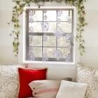 Хвойная гирлянда, бумажные снежинки меняют облик окна. Красная подушка на диване у окна также украшает окно.