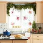 Хвойная гирлянда, елочки в мешочках и красные снежинки на окне.