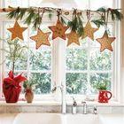 Хвойные веточки и звездочки украшают кухонное окно, цветочные горшки завернуты в красную ткань.