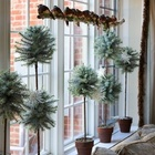 Искусственные елочки разной высоты в горшочках украшают этот подоконник.