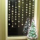 Маленькая елочка у у окна и гирлянды снежинок на окне. Скромно и празднично.