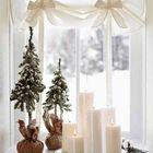 Несколько свечек и несколько искусственных елочек образуют отличную новогоднюю композицию.