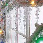 Окно можно украсить заснеженными еловыми веточками, светящейся гирляндой и игрушками в форме сосулек.