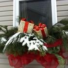 Рождественская композиция из хвои с красным бантом украшенная подарочными коробочками.
