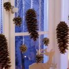 Шишки висящие на окне и фигурки оленей на подоконнике.