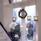 Свечи в разнообразных подсвечниках и рождественский венок выглядят традиционно и празднично.