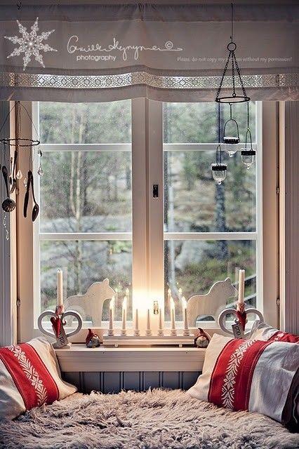 Белые фигурки и свечи украшают это окно.