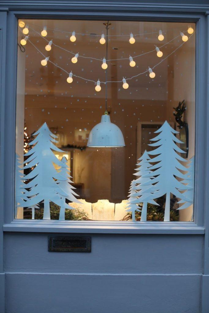 Елочки вырезанные из бумаги и гирлянда украшают это небольшое окно.