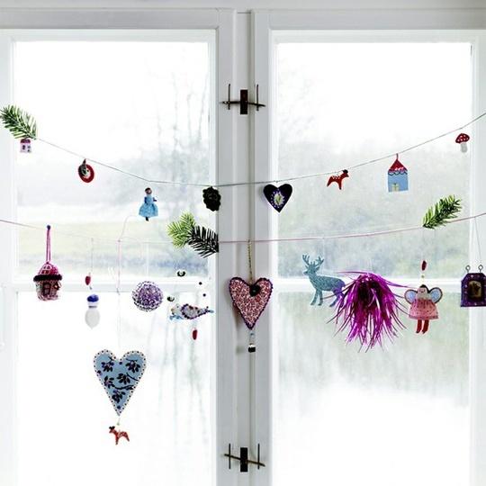 Елочные игрушки на окно можно повесить в виде гирлянд.