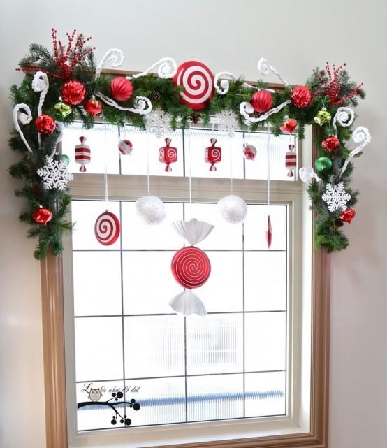 Искусственные конфеты в красно-белых тонах отлично дополнят хвойную гирлянду на окне.