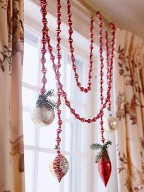 Красная елочная гирлянда и елочные игрушки с веточками хвои висящие на концах гирлянды.