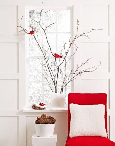 Новогодняя композиция из веточек, елочных игрушек в виде красных птичек и елочных шишек.