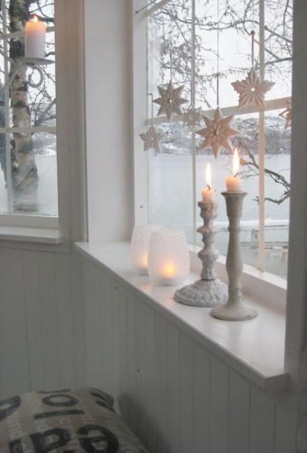 Свечки и снежинки украшают окно и смотрятся там очень логично.