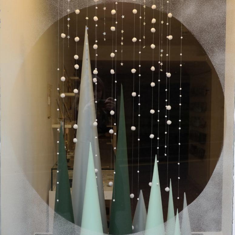 Якобы покрытое инеем окно, на подоконнике разноцветные пирамидки символизирующие елочки и гирлянды из звездочек и шариков.