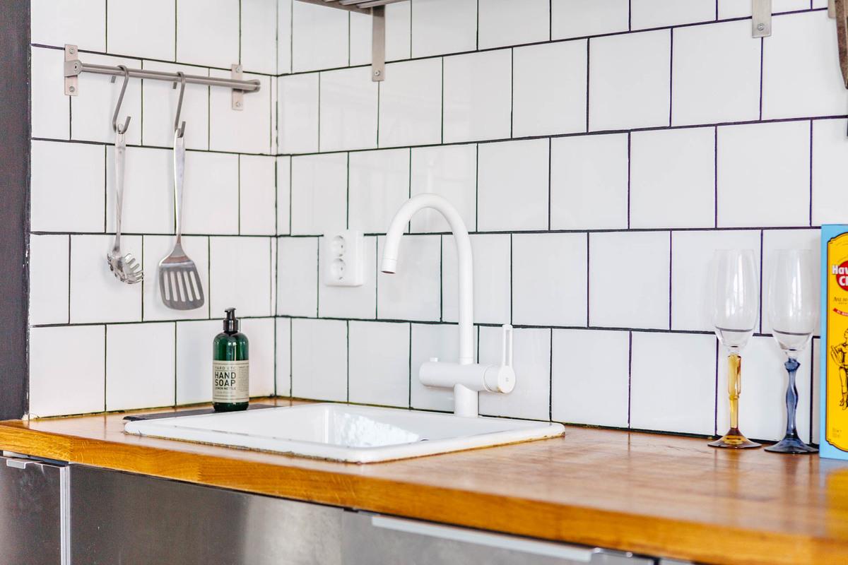 Белый кран буквально растворяется на фоне белой кафельной плитки.